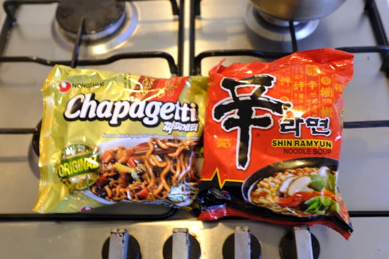 Chapagetti and shin ramyun packets on stove