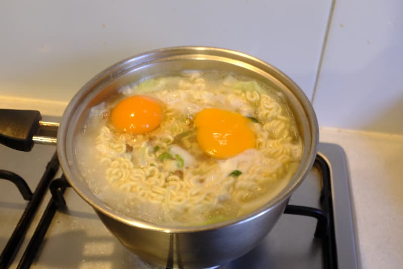 Ramen being cooked with eggs cracked on top